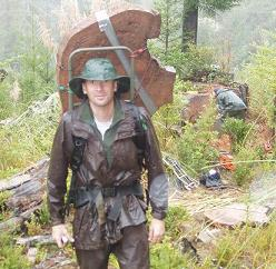 Greg Jennings hiking through mud and rain with a heavy stump fire history sample.